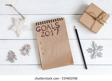 notebook and goals for new year wooden background top view