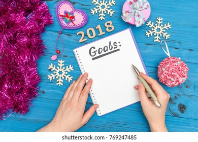notebook with GOALS text and man's hand holding pen above with numbers 2018 and new year ornaments top view