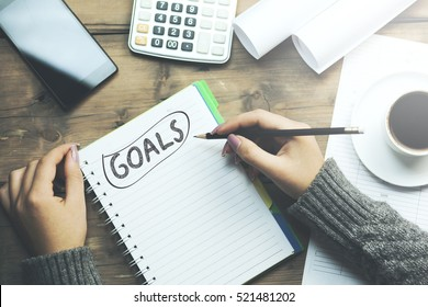 "notebook is with ""GOALS"" text and woman and pencil"