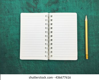 notebook with gold pencil on a green cutting board background.