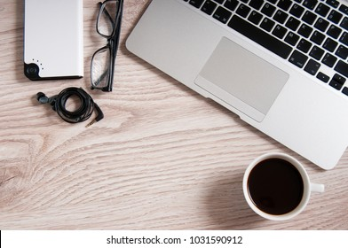 Notebook with hot coffee and flash-payer with headphones on wood table. Home business workplace concept