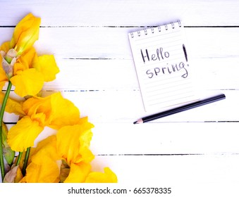 notebook with the inscription hello spring and a bouquet of yellow irises, top view