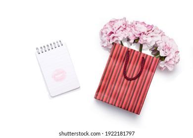 Notebook mit Küssen und Geschenktasche mit Blumen