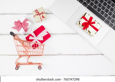 Notebook laptop, gifts box red ribbon, red heart and shopping cart on white wooden background with copy space for text. Shopping online for Christmas new year, Valentine concept .Flat lay, top view.