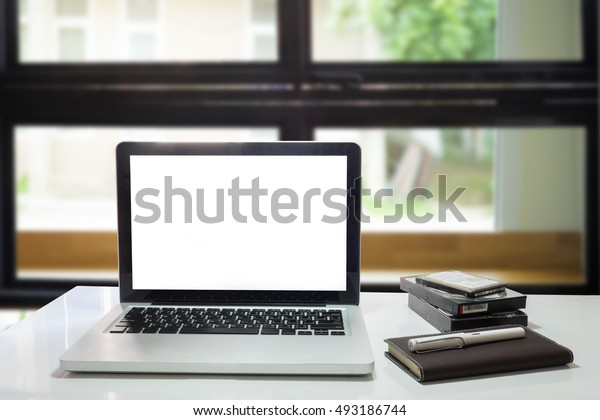 notebook or laptop,pen,notepad and harddisk on wood desk against the window.