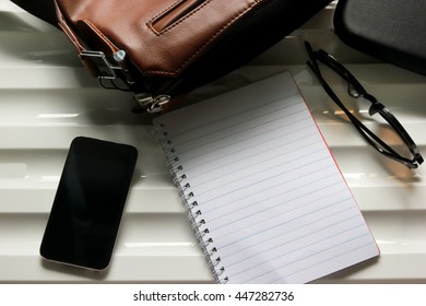 Notebook, leather bag, glasses and smart phone on desk