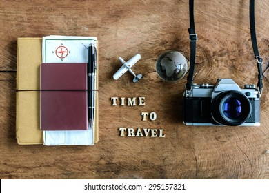 """Notebook with map, passport and camera on wooden background with word """"Time to travel"""""""