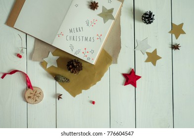 """Notebook with """"Merry Christmas"""" note and ornaments. White and golden stars. Merry Christmas decorative background. Banner, poster or greeting car template on Merry Xmas."""
