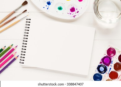 Notebook mock up for artwork with watercolor paints, palette, glass of water and a paintbrushes. View from above. Artistic work tools on white wooden table.