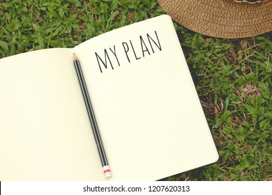 Notebook with my plan text on top of grass, Top view, flat lay.
