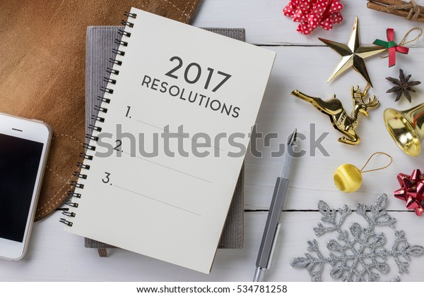 Notebook with New Year's 2017 resolutions and colorful decoration objects.