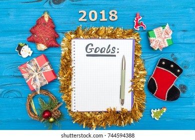 Notebook with new years goals for 2018 with a pen and numbers 2018, gift boxes and New Year ornaments on a blue wooden table seen from above