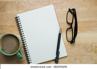 Notebook or note pad,smart phone,cup of coffee and glasses on Brown wooden background top view with copy space. office desk concept