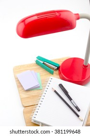 Notebook, note paper, black pencil, pen, table lamp and  stapler on writing table