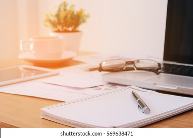 notebook or notepad blank with a pen on top and laptop put on right side, It has been on office desk for work, business concept.