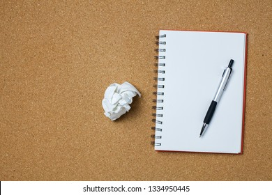 Notebook or notepad paper and pen on a wooden desk.