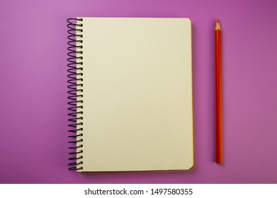 notebook for notes on a metal spiral and a red pencil lie on a lilac background. For your design.