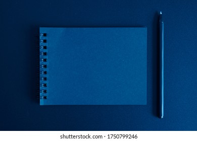 notebook on a spring and a pen on a black background. space for text. toned classic blue color