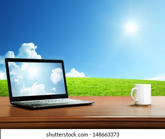 notebook on table and field of spring grass