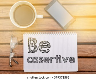 Notebook on table with text about soft competence: Be assertive