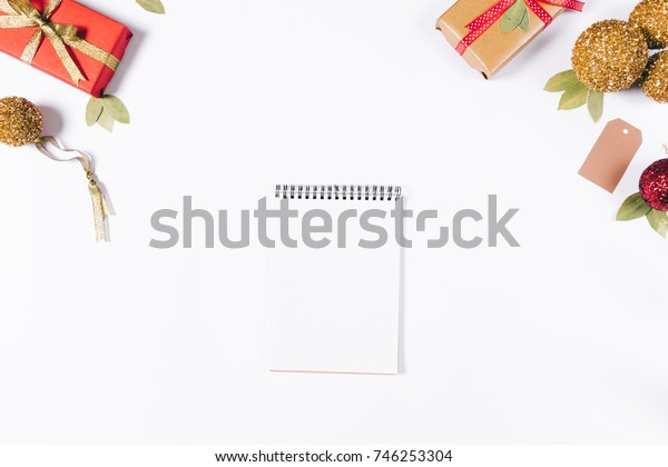 Notebook on a white table among Christmas gifts top view