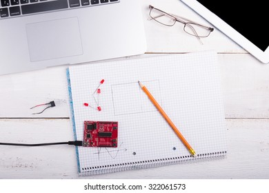 Notebook on a white table with a pen and micro controller programming kit in the middle of the background laptop, tablet, glasses