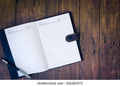 Notebook on a wood table with pen.Top view