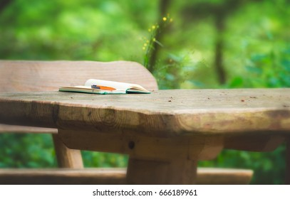 Notebook on wooden bench in a park.