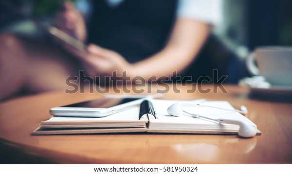 Notebook on a wooden table with blur woman background