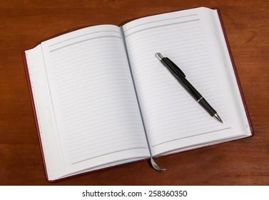notebook on a wooden table. open diary and pen to record