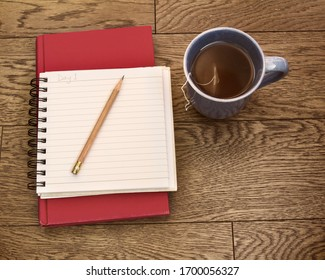 Notebook open with sharp pencil, book and cup of tea; Journal open for reflection with some warm tea