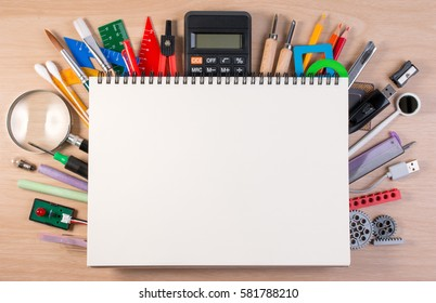 Notebook over school supplies or office supplies on school table. Background with school or office material with copy space for text.