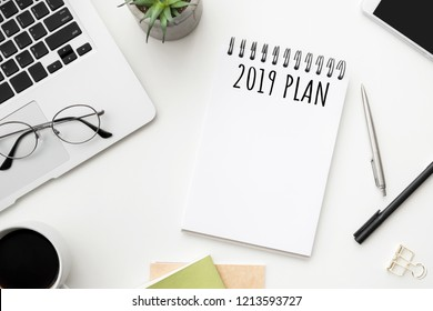 Notebook page with 2019 plan text on white office desk table. Top view, flatl lay.