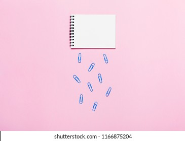 Notebook and paper clips on pink table looks like cloud and rain. Office tools concept. Top view, flat lay