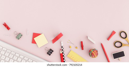 Notebook paper, keyboard, sticky note, pen, ruller, scissors, paper clip on pink background