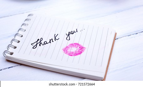 notebook paper with a line with an inscription thank you and kiss imprint of lipstick red lipstick