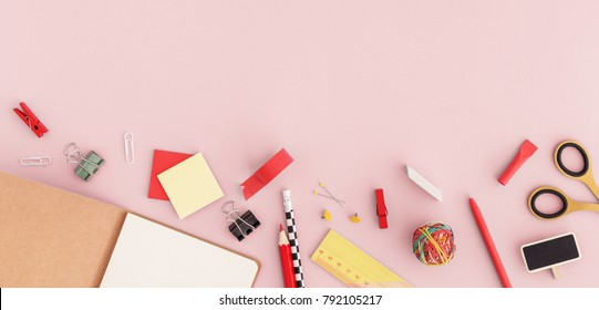 Notebook paper, scissors, sticky note, pen, ruller paper clip on pink background