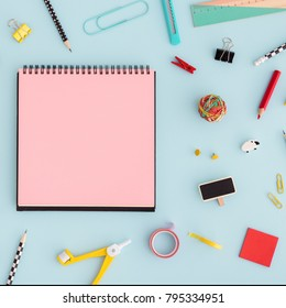 Notebook paper, sticky note, pen, ruller paper clip on pink background