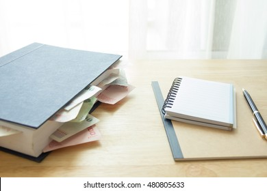 notebook papers with money in book,education make money,natural day light, selective focus, space for copy