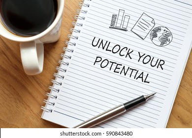 Notebook, pen and a cup of coffee on wooden table. Notebook written Unlock Your Potential, business concept.