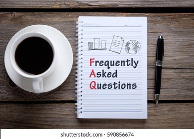 Notebook, pen and a cup of coffee on wooden table. Notebook written FAQ - Frequency Asked Question, business concept.
