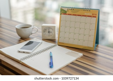 Notebook with pen diary clock smartphone coffee on table with March 2018 calendar at office work place. Planning scheduling agenda, Event, organizer writing detail of plan for 2018. Calendar concept.