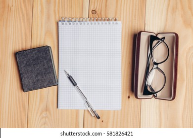notebook, pen and glasses in a case on a wooden background..