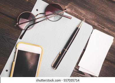 notebook, pen, glasses, cup of coffee on a wooden table phone