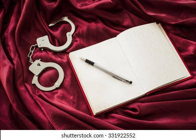 Notebook with pen and handcuffs