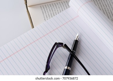 Notebook with a pen and ink and eyeglasses on desk