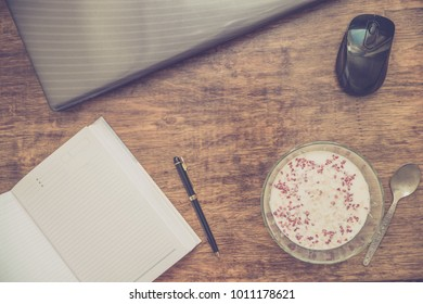 Notebook with pen, laptop, and plate of oat porridge. Concept of office break. Flat lay