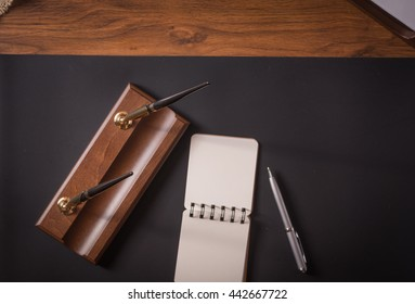 notebook with pen o a leather table