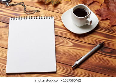 Notebook with pen, old clock, cup of coffee, books and maple leaves, lie on a wooden table. Copy space