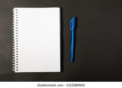 notebook with a pen on dark background